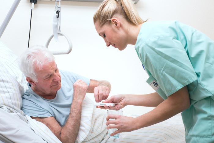 Ein älterer Mann liegt in einem Pflegebett und beugt sich zur Seite. Eine junge Frau reicht ihm ein Glas Wasser und Medikamente.