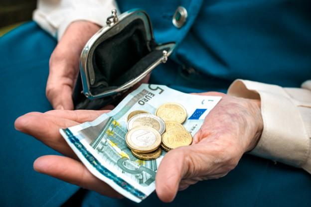 Zu sehen ist eine Hand, die einen Geldschein und ein paar Münzen hält, daneben ein offenes, leeres Portemonnaie.